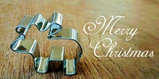 La cartolina con una forma d'argento metallica per i biscotti ed i biscotti sotto forma di renna sta stando su una tavola di legn fotografia stock libera da diritti
