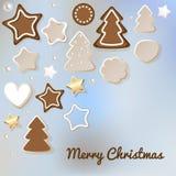 La cartolina di Buon Natale con il pan di zenzero & i biscotti su un bokeh blu annebbiano il fondo royalty illustrazione gratis