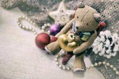 La cartolina di Natale con l'orsacchiotto, collana, pigna, albero di Natale gioca per la vostra progettazione Priorità bassa di n Fotografia Stock