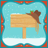 La cartolina di Natale del cowboy con il cappello occidentale ed il legno si imbarcano sul fondo Fotografia Stock