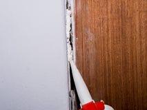 La cartuccia del sigillante del silicone con la pistola del silicone riempie la parete Immagini Stock Libere da Diritti