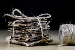 La cartulina junta las piezas apilado y atado con una secuencia del yute Pape inútil fotos de archivo
