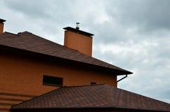 La casa è fornita di tetto di alta qualità delle mattonelle del bitume delle assicelle Un buon esempio di tetto perfetto Il tetto immagini stock libere da diritti