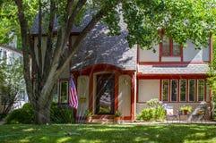 La casa bonita del ladrillo arregló en rojo con el patio y las flores y los árboles grandes que exhibían la bandera americana con fotografía de archivo