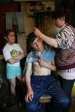 La casa campesina rusa, su madre hace su corte de pelo del hijo Imagenes de archivo