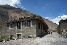 La casa, con legna da ardere sul tetto, contro il contesto della montagna, nel villaggio di Kagbeni, il Nepal Immagini Stock