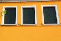 La casa con la pared amarilla pintada y 3 cerraron ventanas Fotos de archivo libres de regalías
