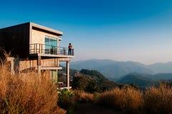 La casa de campo de madera moderna de la cabina en grasshill con la montaña compite fotos de archivo libres de regalías