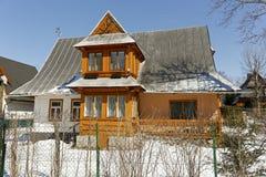 La casa de la familia se cubre con un tejado escarpado imagenes de archivo
