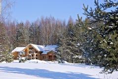 La casa de madera en una madera del invierno Foto de archivo libre de regalías