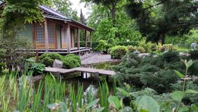 La casa de madera japonesa defiende en silencio la charca entre el verdor almacen de video