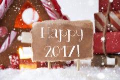 La casa de pan de jengibre con el trineo, copos de nieve, manda un SMS a 2017 feliz Imágenes de archivo libres de regalías