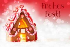 La casa de pan de jengibre, fondo rojo, Fest de Frohes del texto significa Feliz Navidad Fotos de archivo