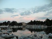 La casa de piedra vieja de Istrian, en una corriente constante del agua, con muchos barcos en el puerto en la oscuridad con una r fotografía de archivo libre de regalías