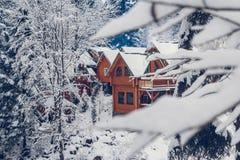 La casa de vacaciones de madera de la cabaña en centro vacacional de la montaña cubrió con nieve fresca en invierno fotografía de archivo