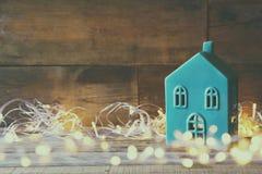 La casa decorativa al lado de la guirnalda del oro se enciende en fondo de madera Copie el espacio Imágenes de archivo libres de regalías