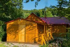 La casa del bagno ha allineato con legno con un tubo di fumo nei precedenti di una foresta verde Immagini Stock