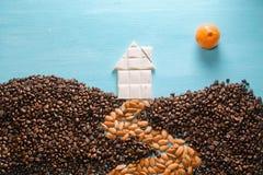 La casa del chocolate blanco, la tierra de los granos de café, el camino de las almendras, el sol de una fruta cítrica en azul Imagenes de archivo