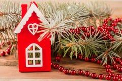 La casa del juguete se coloca cerca de un árbol de navidad Fotos de archivo
