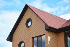 La casa del ladrillo con la ventana del ático y el asfalto rojo escalona el tejado Construcción de la techumbre Fotografía de archivo