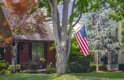 La casa del ladrillo fijó en vecindad tradicional con los árboles grandes un alimentador del pájaro y flores coloridas y una band fotografía de archivo