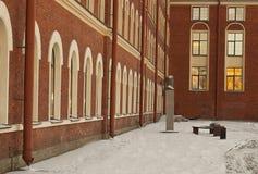 La casa del ladrillo rojo y el monumento delante de él Imágenes de archivo libres de regalías