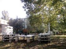 la casa di arte ha fatto il banco di rilassamento con la tavola sotto gli alberi Fotografia Stock