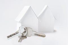 La casa di carta due e le chiavi sulla copia bianca spaziano il fondo Fotografia Stock Libera da Diritti