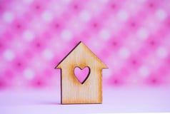 La casa di legno con il foro nella forma di cuore sul rosa ha macchiato il backgrou Immagine Stock