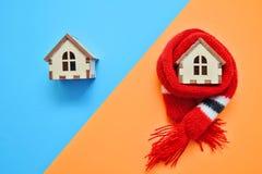 La casa di legno due su colore blu ed arancio, una casa weared sulla sciarpa, concetto per le case dell'isolamento divise diagona immagini stock libere da diritti