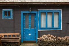 La casa di legno nera tradizionale con il blu ha incorniciato le finestre e la porta, con i motivi floreali Immagine Stock