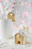La casa di pan di zenzero ha messo sopra una tazza bianca sui precedenti di bokeh e di neve Immagine Stock