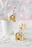 La casa di pan di zenzero ha messo sopra una tazza bianca sui precedenti di bokeh e di neve Fotografie Stock