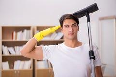 La casa di pulizia dell'uomo con l'aspirapolvere fotografie stock libere da diritti