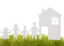 La casa e la famiglia da una carta hanno tagliato sull'erba Immagine Stock