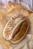 La casa ha fatto l'artigiano acido della pasta ha compitato il pane dopo avere cotto in un forno olandese su fondo di marmo fotografie stock libere da diritti