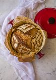 La casa ha fatto l'artigiano acido della pasta ha compitato il pane dopo avere cotto in un forno olandese su fondo di marmo fotografia stock