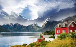 La casa hermosa en un fondo de montañas en Noruega Fotos de archivo libres de regalías