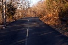 La casa I della strada - Asphalt Highway alla luce solare bronzea di inverno di sera Fotografia Stock