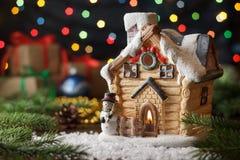 La casa leggiadramente della cartolina di Natale con il pino si ramifica, regali, fondo variopinto delle luci fotografia stock libera da diritti