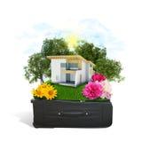 La casa, los árboles y la hierba verde en viaje empaquetan Fotos de archivo