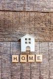 La casa miniatura del modello del giocattolo con la CASA dell'iscrizione segna la parola con lettere su fondo di legno immagini stock libere da diritti
