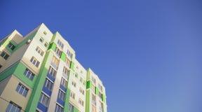 La casa molto-storeyed contro il cielo blu Fotografia Stock