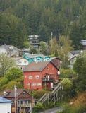 La casa roja grande en abeto cubri? la colina de Alaska Imagen de archivo