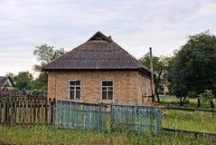 La casa rurale del vecchio mattone dietro un di legno recinta l'erba Fotografia Stock