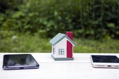 La casa se coloca entre dos teléfonos móviles - blancos y negros Foto conceptual Simboliza la división de propiedades inmobiliari imágenes de archivo libres de regalías