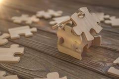 La casa si compone dei pezzi di puzzle, un fondo naturale dell'albero con i raggi del sole Immagini Stock Libere da Diritti