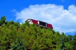 La casa sta sopra una montagna, circondata dalla foresta Fotografia Stock