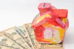 La casa variopinta del moneybox si leva in piedi sui dollari Fotografie Stock
