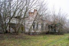 La casa y el pórtico viejos, descuidados, señoriales entre los árboles Textura de la madera agrietada vieja pintada verde Foto de archivo libre de regalías